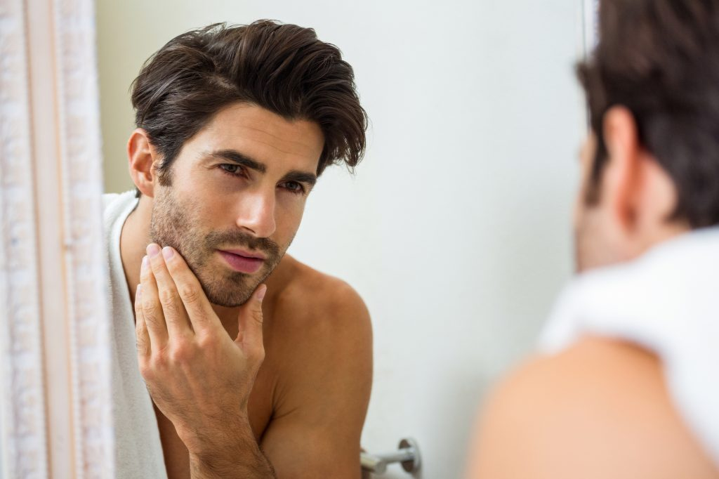 Young,Man,Looking,In,Mirror,And,Checking,His,Stubble,In